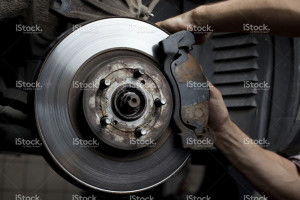 image of mechanic working on brake disc and caliper