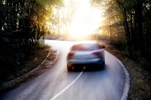 image of car speeding around bend on country road with sun shining through trees.