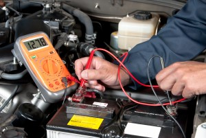Image of a mechanic using a multi-meter to check the voltage of a car battery.