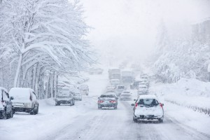 Image of traffic struggling through snow and ice in freezing winter weather, slick, snowy roads.