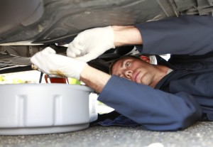 image - mechanic laying under car draining oil into a pan.