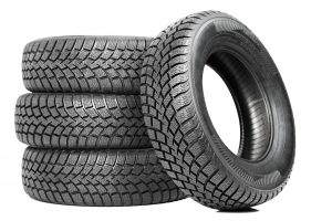 image - Stack of three tires, fourth tire leaning against stack