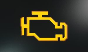 image - An extreme closeup of an illuminated yellow-orange check engine indicator dashboard light isolated on black background.