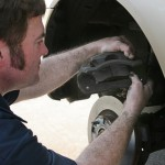 image of an auto mechanic working on disc brakes, inserting new brake pads in the caliper.
