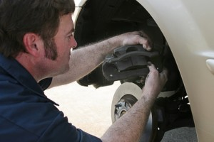 An auto mechanic working on disc brakes,  inserting new brake pads in the caliper.