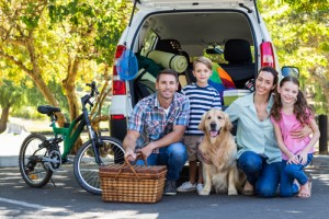 image of happy family in front of car.