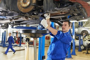 image - mechanic working on underside of car on lift in repair shop.