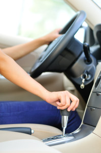 Image of person driving manual transmission, shifting gears.