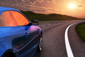 Image of car driving on curved road into sunset.