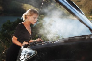 Image - woman looking at engine overheated and smoking, hood up.