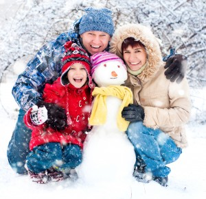 Image - Family having fun in the snow, posing with snowman.