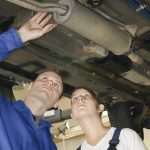image - Mechanic and customer looking at exhaust system under car on lift
