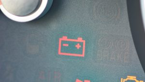 image of closeup on dashboard battery warning light.