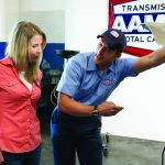 image of happy customer and AAMCO mechanic looking at engine