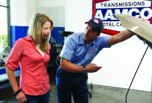 image of AAMCO mechanic talking with customer, discussing engine and repairs under the hood of her car.