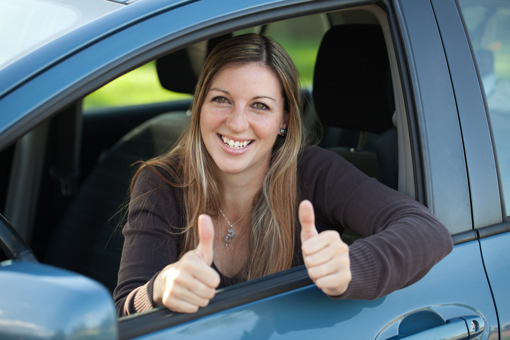 image of happy customer sitting in her car, leaning out driver's window, giving two thumbs up.