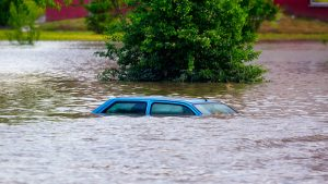 image of car submerged in flood water on town street.