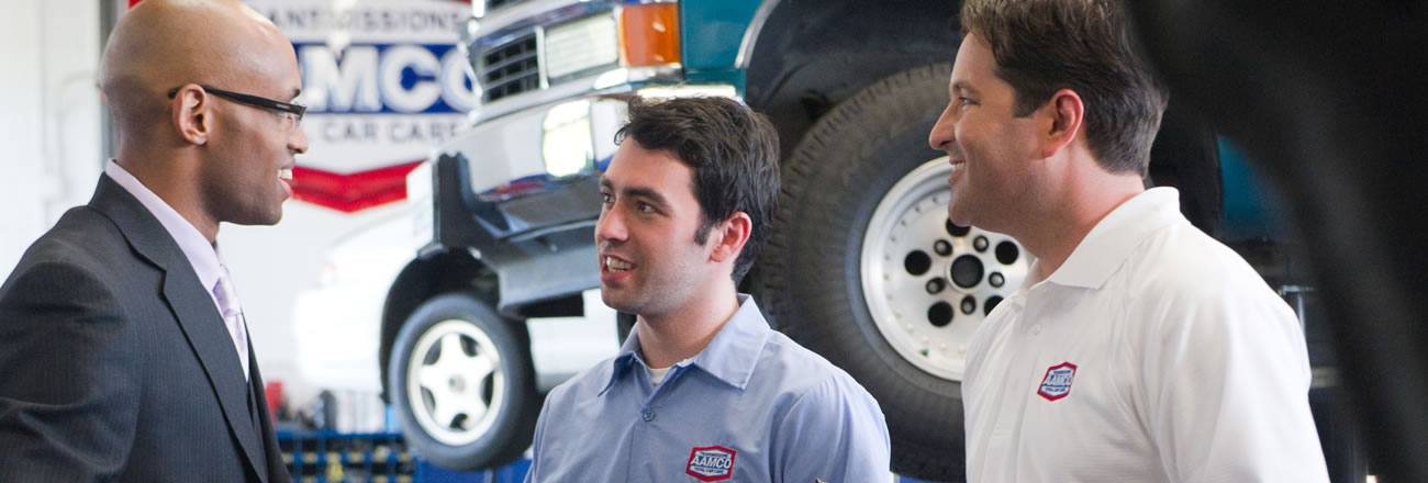 image of AAMCO technician and service center manager talking with happy customer.